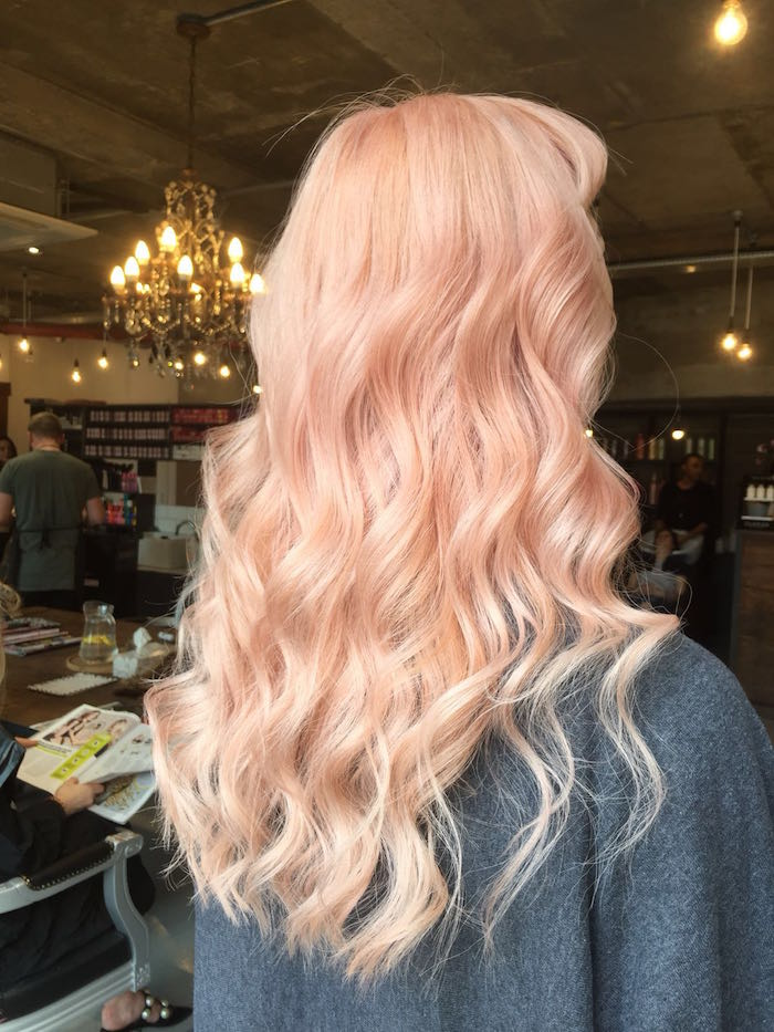 Soft pastel peach hair with waves at a salon with a light