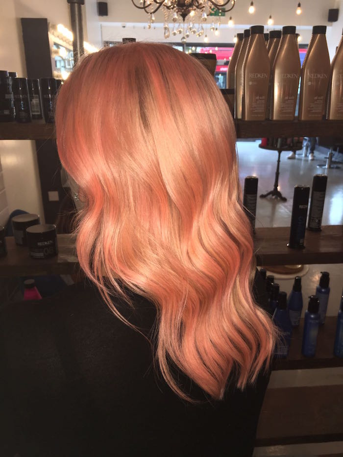 Shiny peach hair at Brixton salon in London against product display